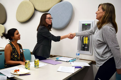 Mallory Garner-Wells shaking hands with Boulder attendees at advocacy training