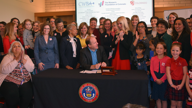 Governor Jared Polis signs Equal Pay for Equal Work Act at WFCO offices
